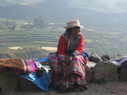 peruvian national sitting on rock edge by Insider Tours